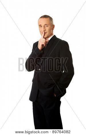 Mature businessman gesturing silent sign.