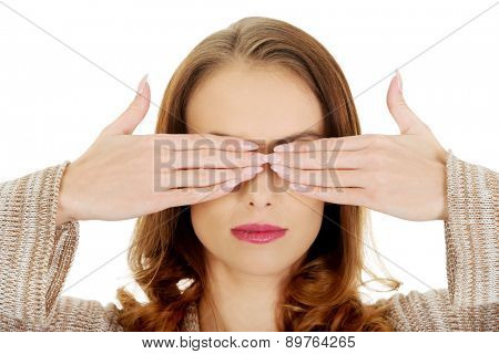 Beautiful woman covering eyes with her hands.