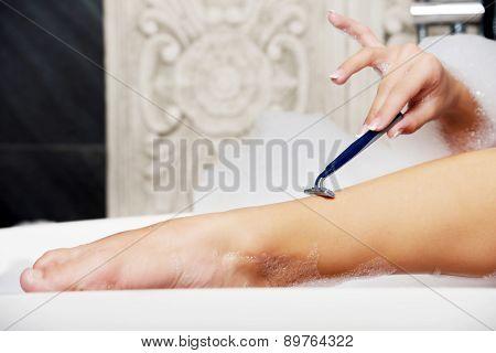 Woman shaving her leg with razor in bathroom.