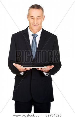 Happy mature man using digital tablet.
