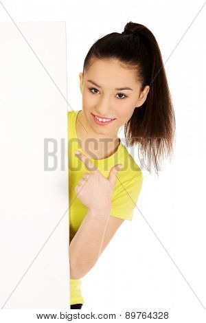 Young happy teenage woman pointing on blank board.