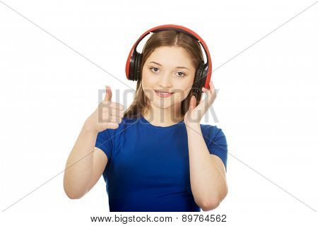 Teenage woman with music headphones and thumbs up.