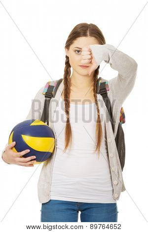 Teenager with volley ball and thumbs down.