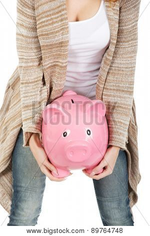 Casual woman holding piggy bank.