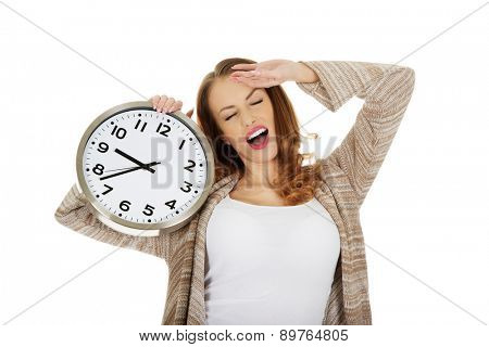 Beautiful yawning woman with clock.