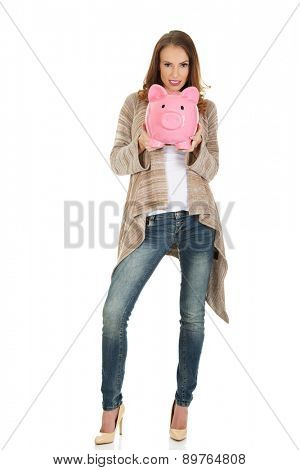 Beautiful casual woman holding piggy-bank.