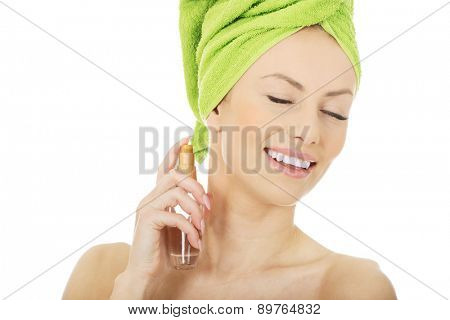 Woman in towel turban applying parfume.
