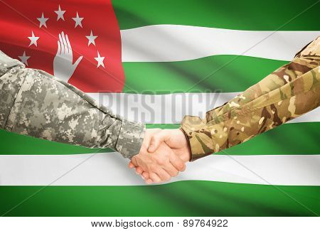 Men In Uniform Shaking Hands With Flag On Background - Abkhazia