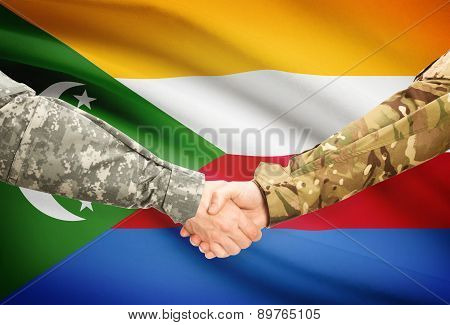 Men In Uniform Shaking Hands With Flag On Background - Comoros