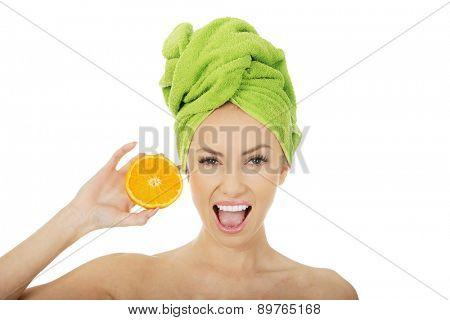 Beautiful happy woman holding an orange.