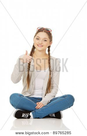 Teen woman sitting in sunglasses with thumbs up.