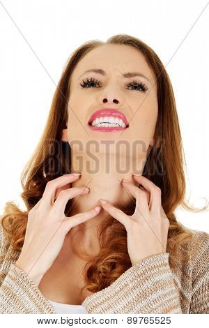 Woman suffering from throat pain.