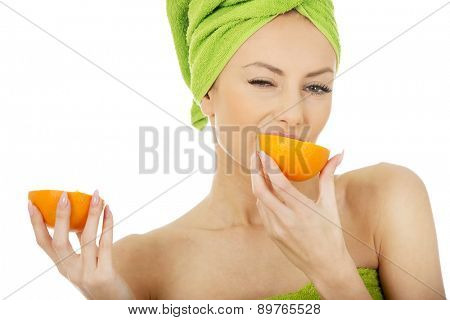 Beautiful happy woman eating an orange.