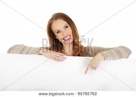 Beautiful happy woman pointing on blank board.