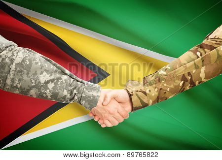 Men In Uniform Shaking Hands With Flag On Background - Guyana