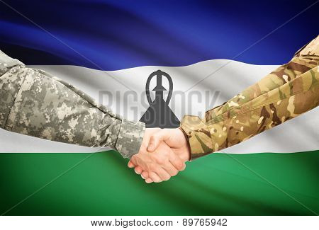Men In Uniform Shaking Hands With Flag On Background - Lesotho