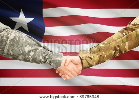 Men In Uniform Shaking Hands With Flag On Background - Liberia