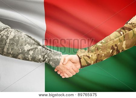 Men In Uniform Shaking Hands With Flag On Background - Madagascar