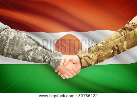 Men In Uniform Shaking Hands With Flag On Background - Niger