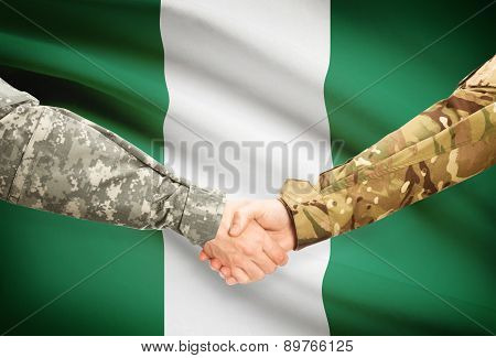 Men In Uniform Shaking Hands With Flag On Background - Nigeria