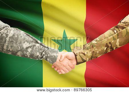 Men In Uniform Shaking Hands With Flag On Background - Senegal