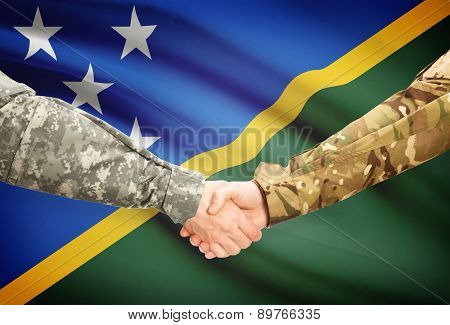 Men In Uniform Shaking Hands With Flag On Background - Solomon Islands