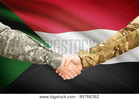 Men In Uniform Shaking Hands With Flag On Background - Sudan