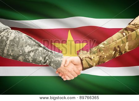 Men In Uniform Shaking Hands With Flag On Background - Suriname