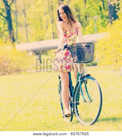 Young woman in short colorful dress with long hair rides a bicycle tour summer city park, look and laughs to camera colour. Altered toned photo