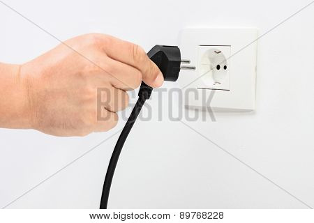 Angle shot of a Caucasian hand plugging in an electric cord into a white plastic socket