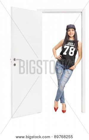 Full length portrait of a young woman in hip hop clothes posing by an open door isolated on white background