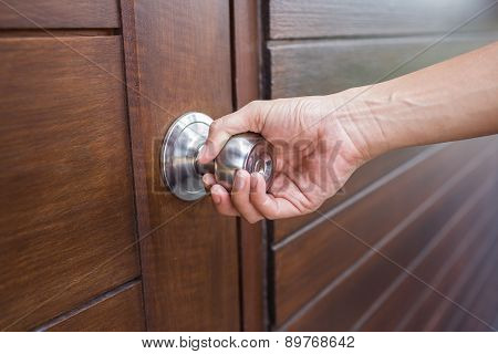 Hand holding a handle of a wood door