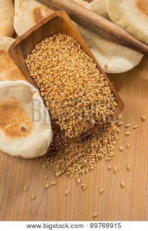 Baked flat-bread, whole wheat grains and rolling pin from top view.