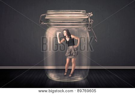 Businesswoman trapped into a glass jar concept on background