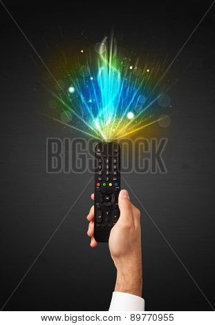 Hand holding a remote control, shining and explosive signal coming out of it