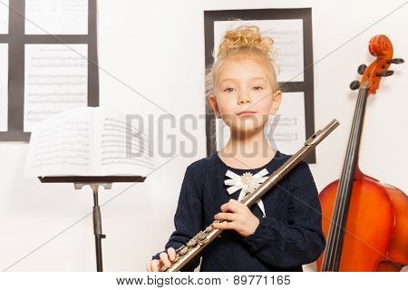 Small blond girl with flute stands near the cello