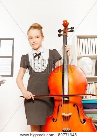 Beautiful girl holding and playing violoncello