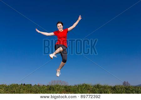 Teenage girl jumping, running outdoor against blue sky