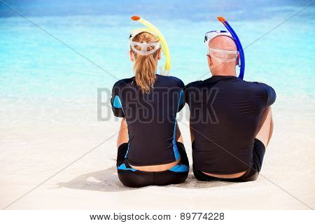 Back side of happy diver couple sitting on the beach and enjoying beautiful sea view, wearing diving equipment and preparing to snorkeling, active summer vacation