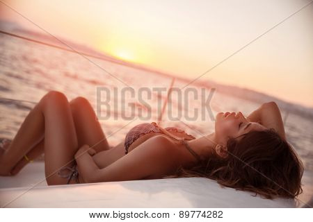 Sexy woman on sailboat lying down on the deck of luxury sailboat, tanning on mild sunset light, enjoying sea cruise, fashion and summer holidays concept