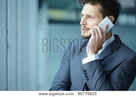 Businessman talking on mobile phone in office lobby