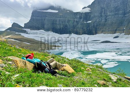 Female Hiker Resting By The Grinnell Glacier In Many Glaciers, Glacier National Park, Montana