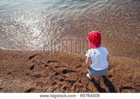 Cute boy playing and having fun on the beach. Little boy playing in the pebbles on the beach in the