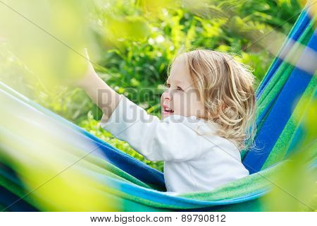 Two Year-old Toddler Girl Is Laughing And Playing In Striped Blue-green Brazilian Hammock