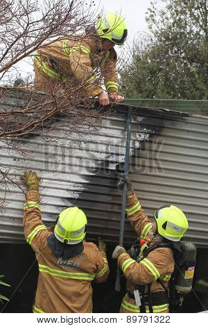 Fire fighters supporting colleague on roof