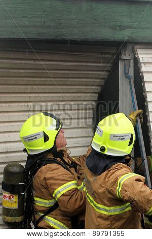 Fire fighters using a crow bar to gain access