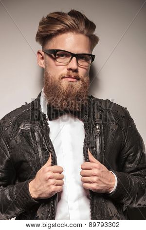 Portrait of a hipster business man pulling his collar while looking at the camera.