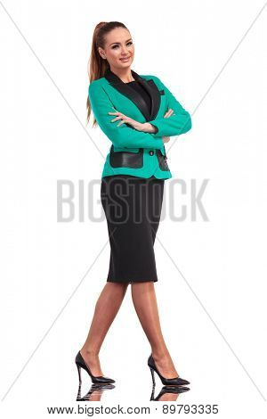 Full body picture of a confident young business woman standing on isolated background with her hands crossed.