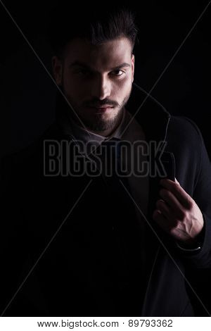 Close up picture of a handsome young business man holding his hand on the collar while looking at the camera, on dark studio background.