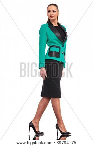 Confident young business woman walking on isolated background, looking up.